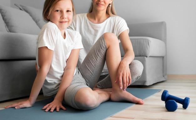 Mutter und mädchen trainieren mit gewichten auf matte