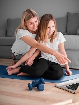 Mutter und mädchen trainieren nach videos