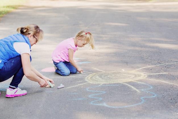 Mutter und mädchen zeichnen mit kreide auf pflaster