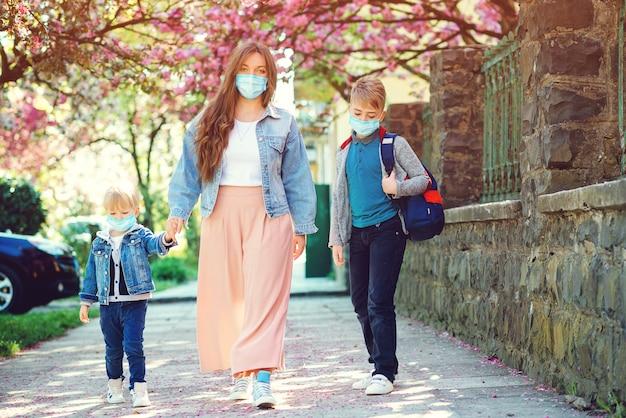 Mutter und schüler der grundschule gehen hand in hand. traurige familie, die während der quarantäne nach hause geht.