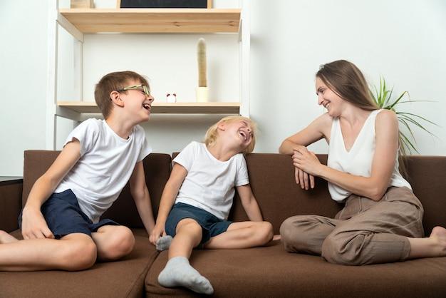 Mutter und söhne sitzen auf der couch und haben spaß beim reden