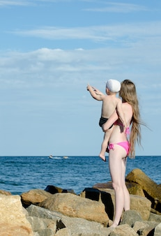Mutter und sohn an den händen sind unter den steinen am meer, zeigen in der ferne