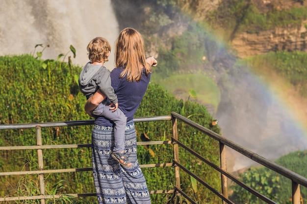 Mutter und sohn auf der oberfläche der majestätischen landschaft des elefantenwasserfalls im sommer in der provinz lam dong, dalat, vietnam