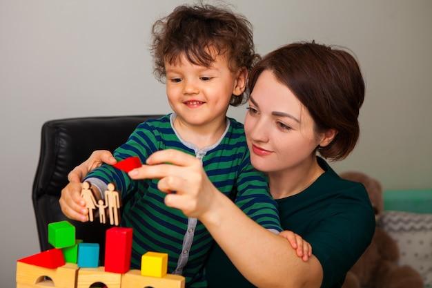 Mutter und sohn bauen ein haus für die familie. sie setzen ein dach. eine frau zeigt und lehrt den jungen, wie wichtig es ist, zu hause unter quarantäne zu stellen.