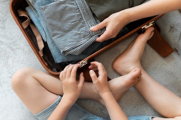 Mutter und sohn bereiten einen koffer für ihren urlaub vor