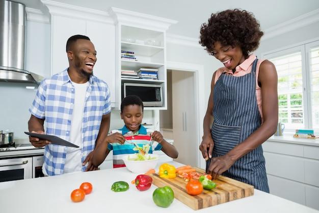 Mutter und sohn bereiten salat vor, während vater digitales tablett in der küche verwendet