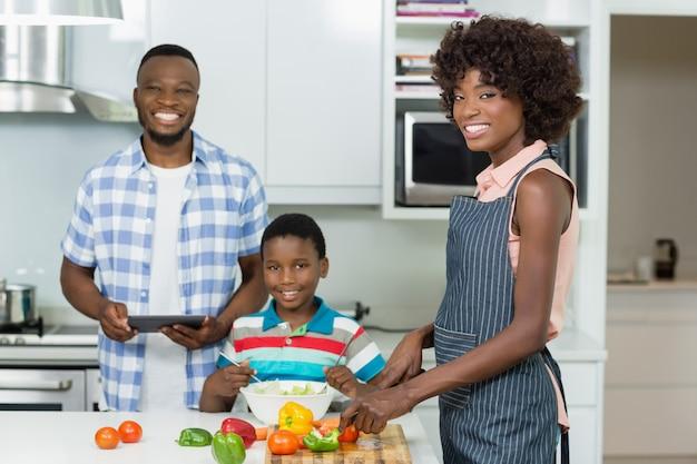 Mutter und sohn bereiten salat vor, während vater digitales tablett in der küche zu hause verwendet