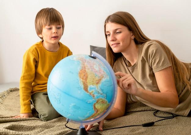 Mutter und sohn betrachten globus zusammen