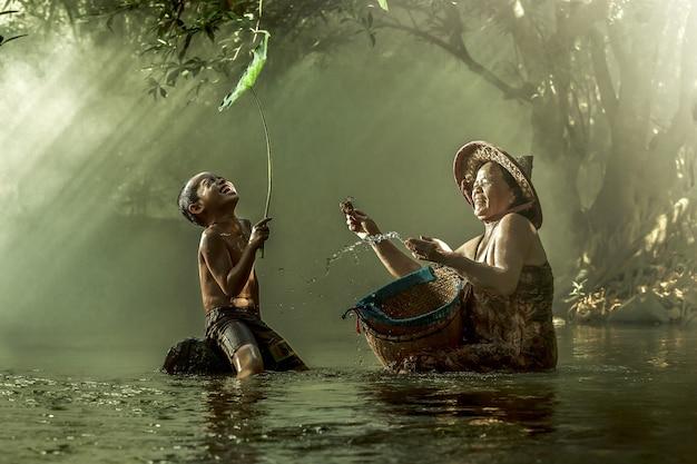 Mutter und sohn, die an einem strom lächeln.