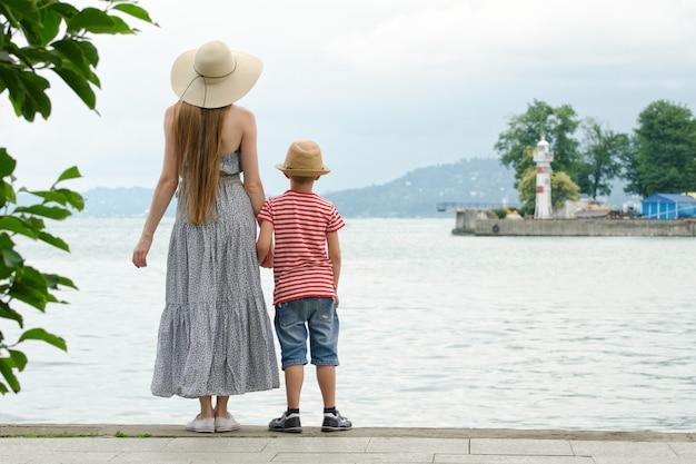 Mutter und sohn, die auf dem pier auf dem seehintergrund, dem leuchtturm und den bergen im abstand stehen