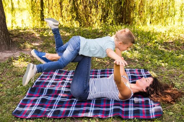 Mutter und sohn, die auf picknickdecke spielen