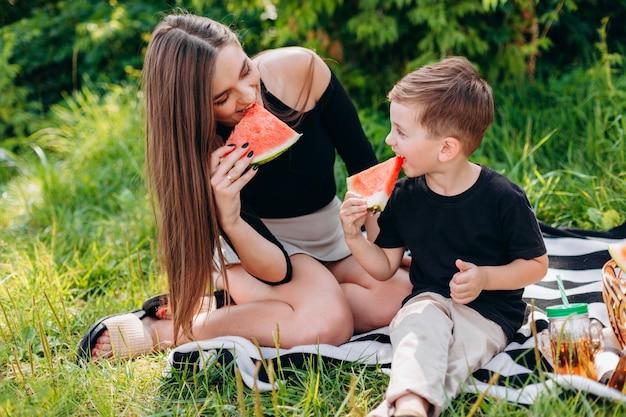 Mutter und sohn, die ein picknick im park haben, essen eine wassermelone.