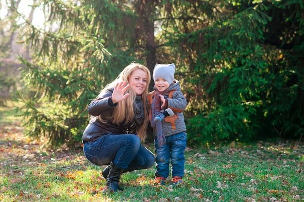 Mutter und sohn, die im herbst park spielen
