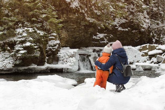 Mutter und sohn, die in der umarmung auf einem hintergrund des schnees sitzen