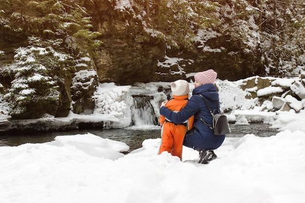 Mutter und sohn, die in der umarmung auf einem hintergrund von schneebedeckten wasserfall-, hügel- und kiefernwäldern sitzen.