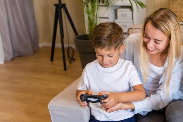 Mutter und sohn, die mit einem gamepad spielen