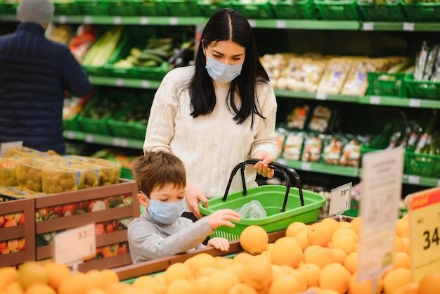 Mutter und sohn, die schutzmasken tragen, wählen früchte aus, die sie im laden kaufen möchten