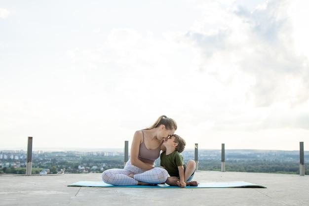 Mutter und sohn, die übung auf dem balkon auf einer stadt während sonnenaufgang oder sonnenuntergang, konzept eines gesunden lebensstils tun.