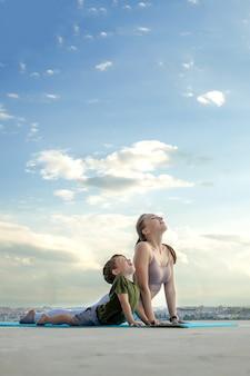 Mutter und sohn, die übung auf dem balkon im hintergrund einer stadt während sonnenaufgang oder sonnenuntergang, konzept eines gesunden lebensstils tun.