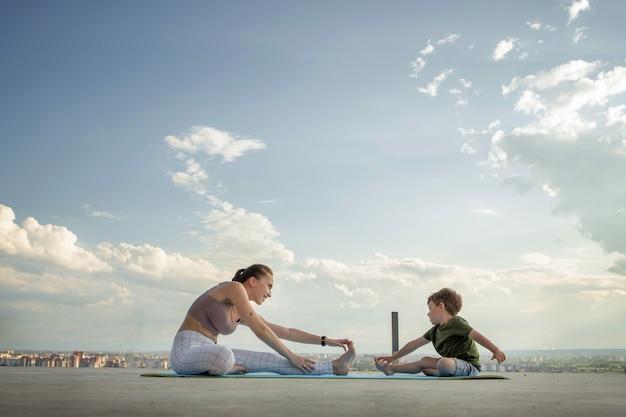 Mutter und sohn, die übung auf dem balkon im hintergrund einer stadt während sonnenaufgang oder sonnenuntergang tun