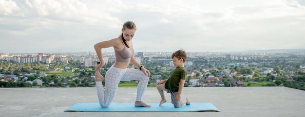 Mutter und sohn, die übung auf dem balkon in einer stadt während sonnenaufgang oder sonnenuntergang, konzept eines gesunden lebensstils tun.