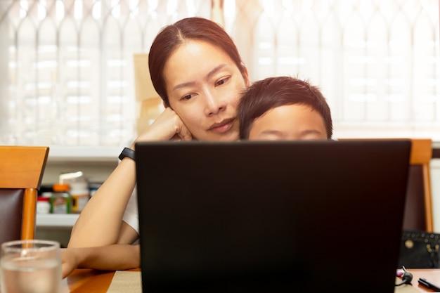 Mutter und sohn, die zu hause am abendtisch sitzen und laptop verwenden