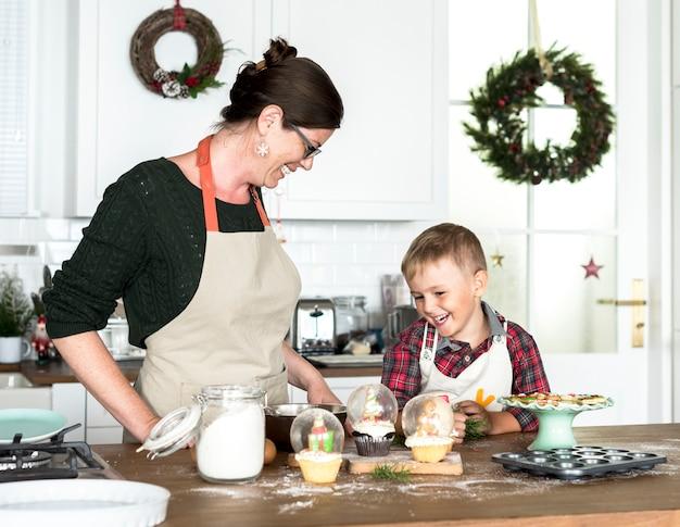 Mutter und sohn, die zu weihnachten in der küche backen