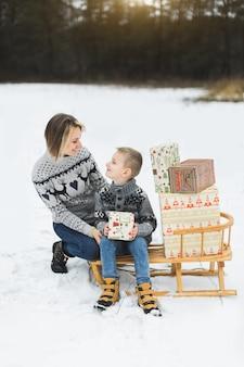 Mutter und sohn draußen sitzen auf holzschlitten mit weihnachtsgeschenken verziert