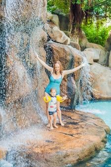 Mutter und sohn entspannen sich unter einem wasserfall im aquapark