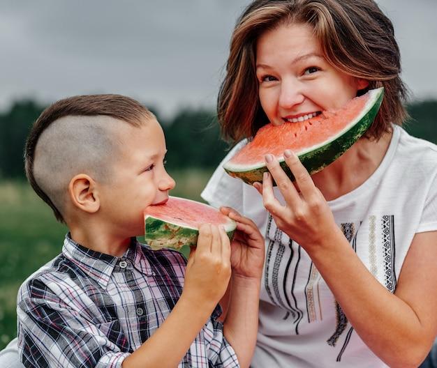 Mutter und sohn essen wassermelone in wiese oder park. glückliche familie beim picknick. porträt im freien
