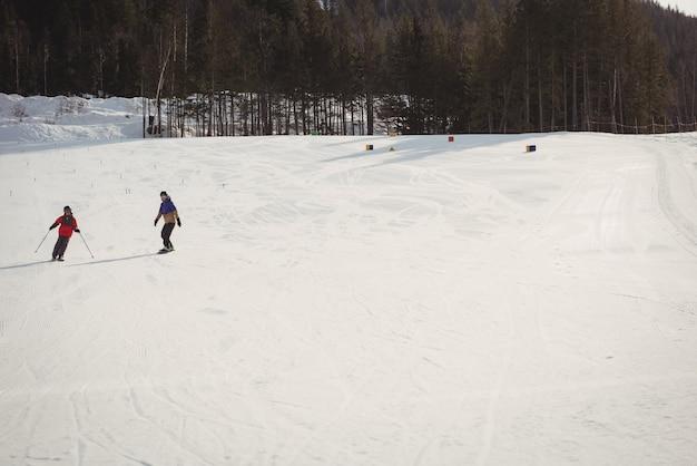 Mutter und sohn fahren auf schneebedeckten alpen ski