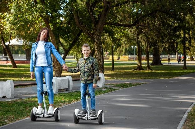 Mutter und sohn fahren ein hoverboard im park