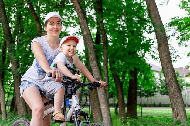 Mutter und sohn fahren fahrrad, mutter trägt im sommer ein kind in einem kinderstuhl auf einem fahrrad im park.