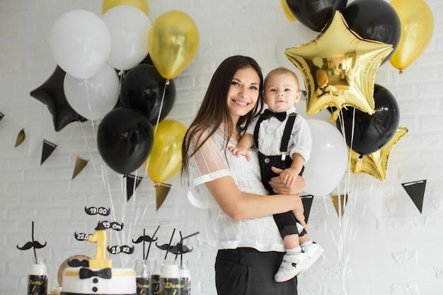 Mutter und sohn feiern den 1. geburtstag zusammen lachen und lächeln mit luftballons, einem schokoriegel.