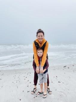 Mutter und sohn gehen am nebligen strand entlang und machen ein foto am telefon. porträt des glücklichen mutter- und kinderjungen des bewölkten wetters gemacht mit telefon. familienzeit zusammen.