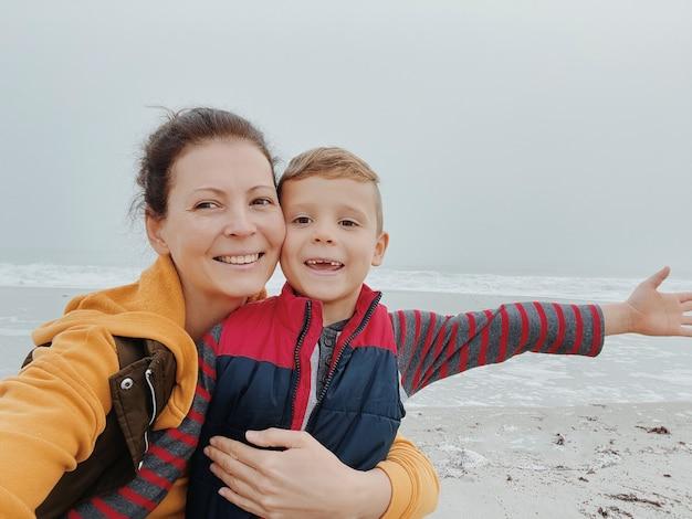 Mutter und sohn gehen am nebligen strand entlang und machen ein selfie am telefon. porträt des glücklichen jungen der mutter und des kindes.