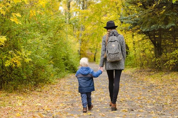 Mutter und sohn gehen im herbstwald spazieren