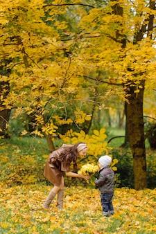 Mutter und sohn gehen spazieren und haben gemeinsam spaß im herbstpark.