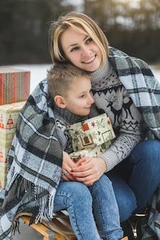 Mutter und sohn genießen den verschneiten wintertag im freien, sitzen auf dem schlitten und umarmen sich