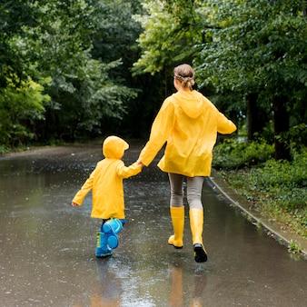 Mutter und sohn halten hände beim tragen von regenmänteln