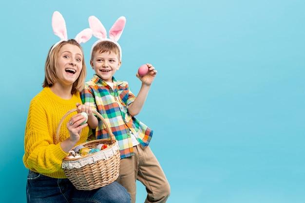 Mutter und sohn im kopierraum zeigen bemalte eier