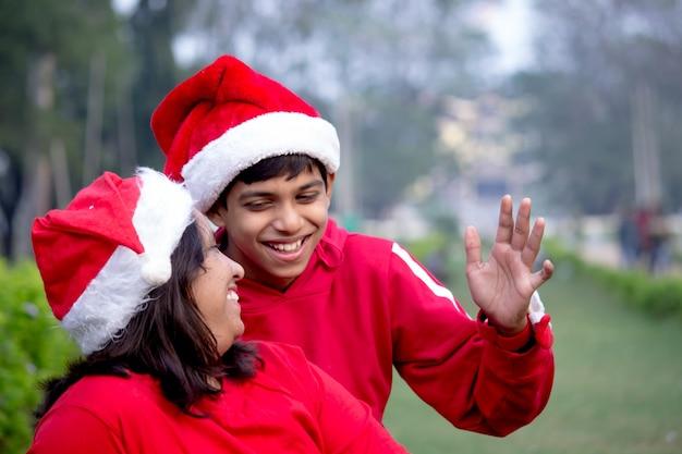 Mutter und sohn in fröhlicher stimmung mit weglächelnden weihnachtsmützen - weihnachtszeit
