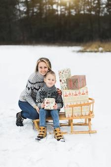 Mutter und sohn in gestrickten pullovern sitzen auf holzschlitten mit geschenkboxen