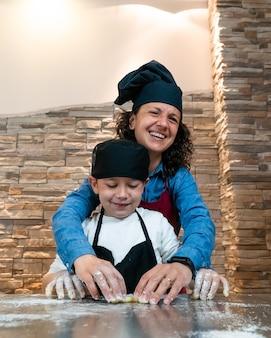 Mutter und sohn kochen gemeinsam ein gebäck in kochkostümen