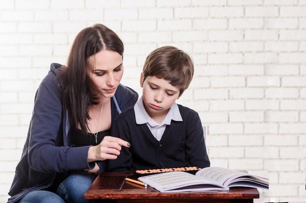 Mutter und sohn lesen ein buch auf dem tisch.