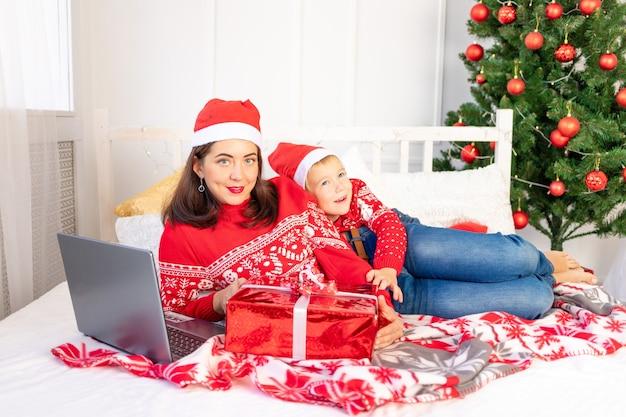 Mutter und sohn liegen auf dem bett in der nähe des weihnachtsbaumes