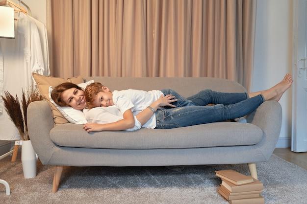 Mutter und sohn liegen auf dem sofa, während sie sich umarmen, fauler tag, mutter und kind momente