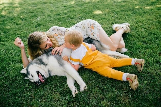 Mutter und sohn liegen mit einem hund im gras