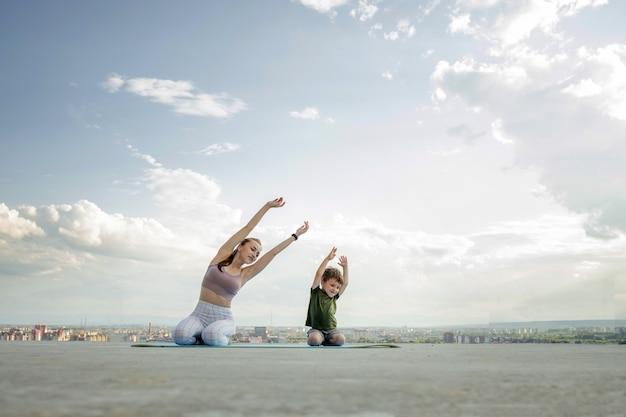 Mutter und sohn machen übung auf dem balkon im hintergrund einer stadt