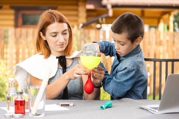 Mutter und sohn machen zu hause physikalische experimente. eine erfahrung mit einem kind darüber, welche der kugeln leer oder mit wasser ist, wird schneller aus feuer platzen. schritt 2